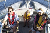 Adult male (dad) wearing an inflatable life jacket driving a motor boat with a boy in a children's life jacket sitting on an adult female's (mom) lap. A girl is is sitting in the back of the boat.